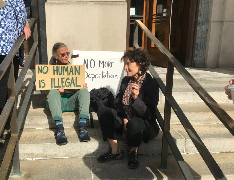 Two of about a dozen supporters of Guzman-Lopez sit outside of the U.S. District Court for the Northern District of New York in Binghamton on Friday after the 32-year-old was sentenced to time served.