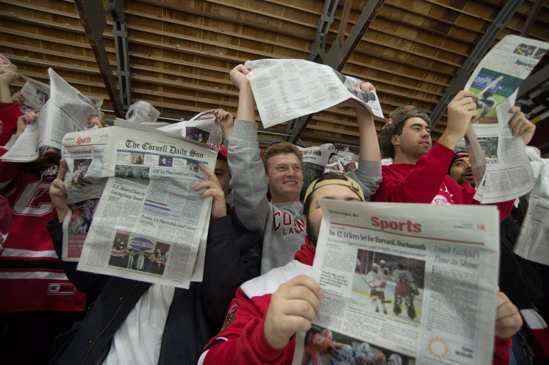"""As the starting lineup of the Harvard men's hockey team (not shown) is read, raucous Cornell fans shake copies of The Cornell Daily Sun while chanting """"Boring! Boring!"""" before throwing the papers over the boards at the team. The Cornell men's hockey team would go on to beat Harvard 3-2 in that contest, the Red's first victory against Harvard since 2015. (Cameron Pollack / Sun Photography Editor)"""