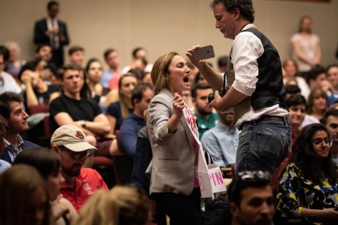 A protester interrupts Cheney's speech while displaying a banner.