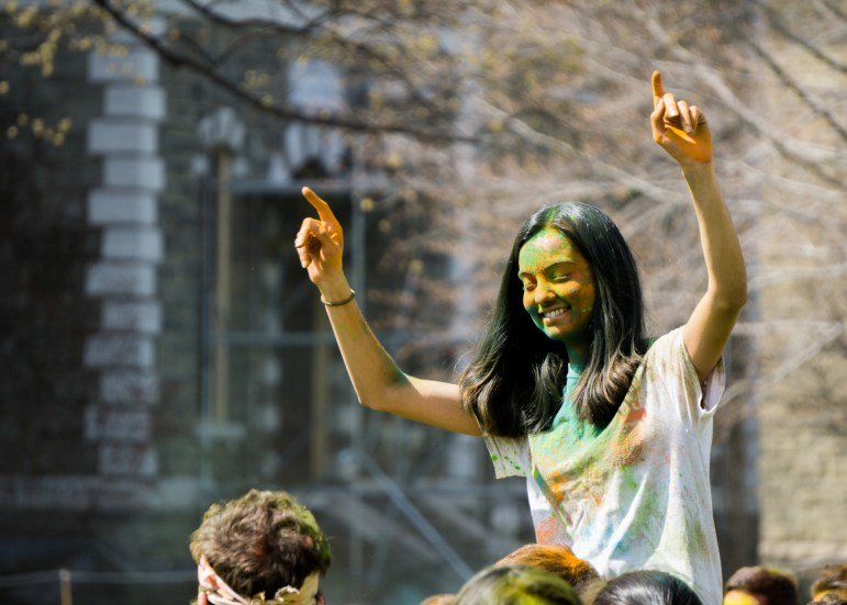 A student rides on the shoulders of a classmate during the Holi celebration at the Arts Quad on Saturday.
