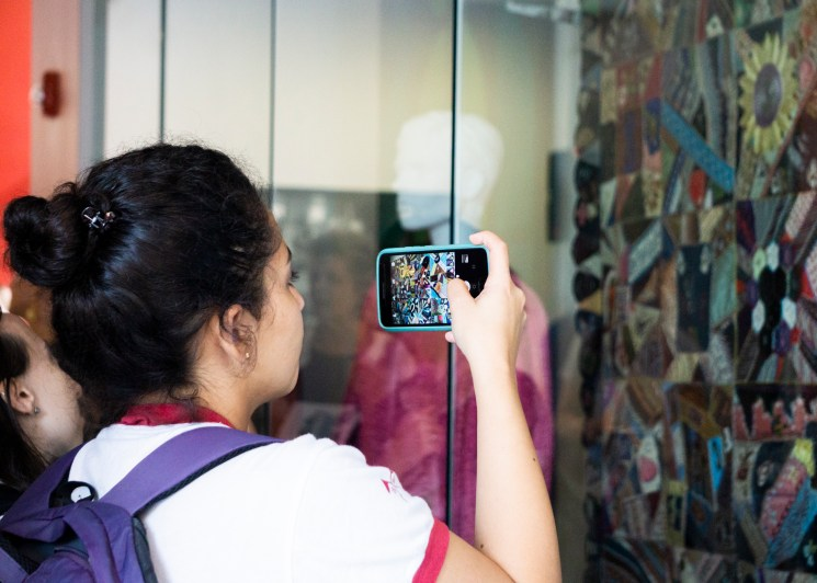 """A student takes a picture of a Bandhani textile, a traditional Indian creation and part of the """"Soft and Squishy"""" display."""