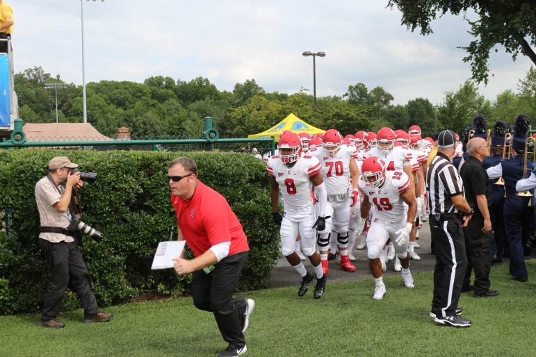 Head coach David Archer '05 leads his team onto the field for the second consecutive year in Delaware.