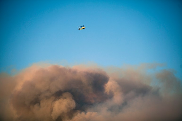 A helicopter flies above the roiling smoke from the Woolsey Fire near Thousand Oaks, Calif., on Nov. 9.