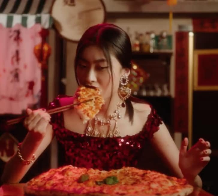 A Chinese woman in Dolce & Gabbana's ad eating pizza with chopsticks.