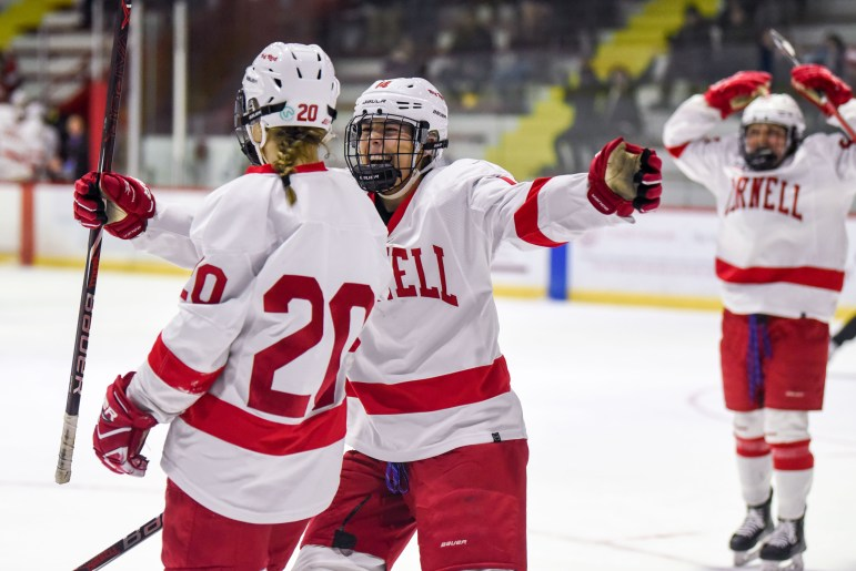 The women's hockey team celebrates after junior forward and co-captain Kirstin O'Neill scores a goal to put the Red up 5-0 over RPI. (Boris Tsang / Sun Assistant Photography Editor)