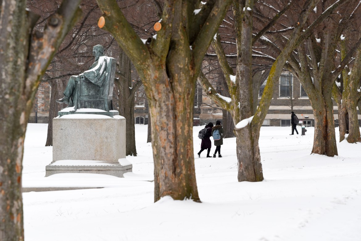 Students make their way to class through the accumulated snow on the Arts Quad.