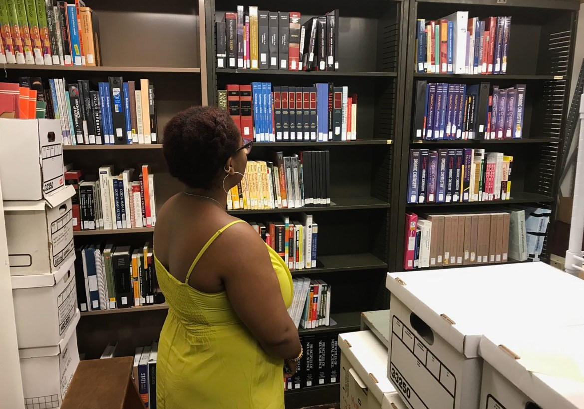 Jaelle Sanon '19 sets up books in the lending library.