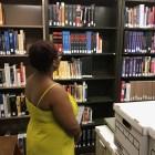 Jaelle Sanon '19 sets up books in the lending library.