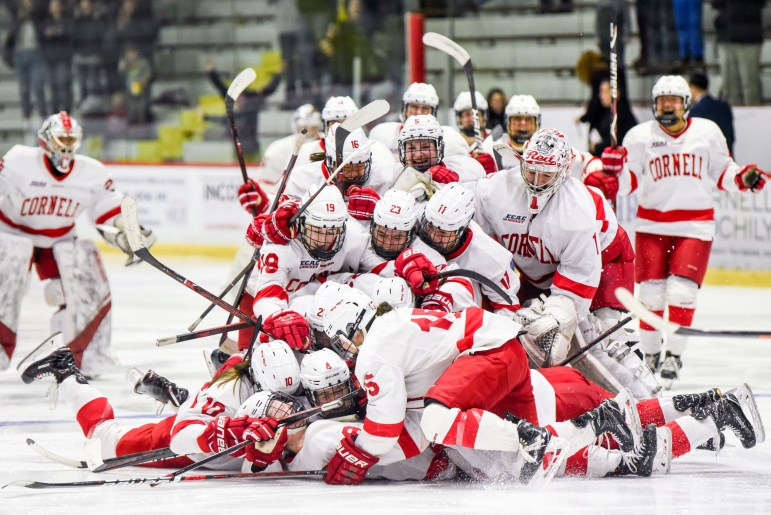 The women's hockey team piles on top of senior defenseman and captain Micah Zandee-Hart after her game-winning goal over Princeton in the second overtime period of the ECAC semifinals. (Boris Tsang / Sun Photography Editor)