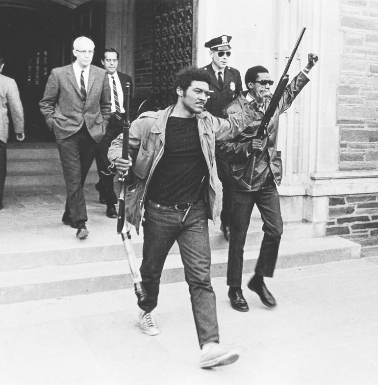 Tom Jones '69 and  Larry Dickson '70 raise clenched fists in triumph as they march out of Willard Straight Hall after the takeover.