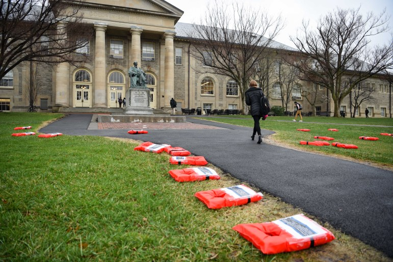 """Cornell Welcomes Refugees (CWR) partnered with 12 other student groups to organize the """"Week of Action for Refugees"""". Life jackets with testimonials of refugees were placed on the Arts Quad as part of the initiative. (Boris Tsang / Sun Photography Editor)"""