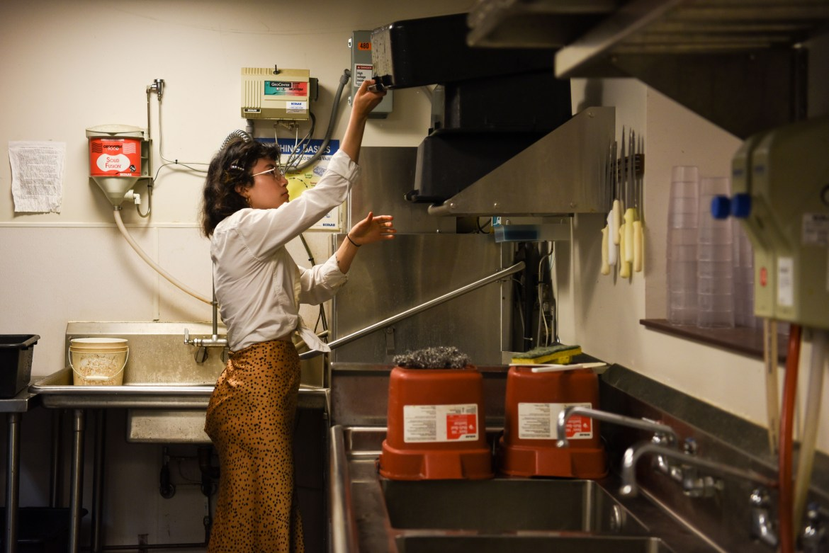 Nicole Oliveira '20 working in the kitchen at Temple of Zeus, one of her multiple jobs on campus.