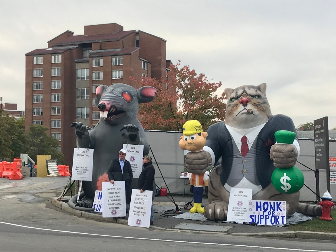 "In addition to Scabby, an inflatable ""Fat Cat"" that held a bag of money in one hand and a construction worker in the other caught the attention of many passersby."