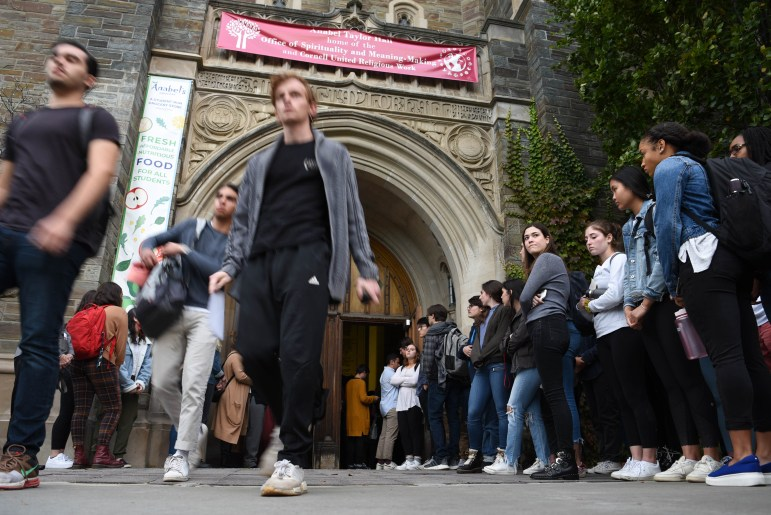 Students stream out of Anabel Taylor Hall after the service of remembrance for Antonio Tsialas '23 on Tuesday. Other students, pictured to the right, lined up to meet with Tsialas's family. (Boris Tsang/Sun Photography Editor)