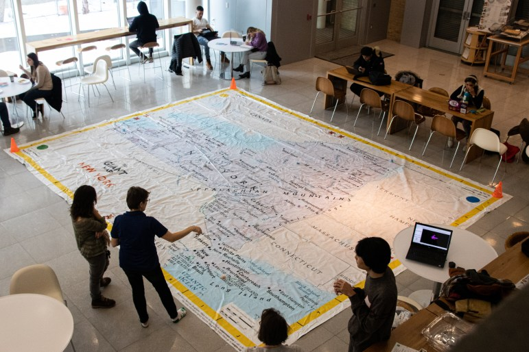 On Tuesday, a 15'-by-20' fabric map covered the floor of the atrium in Martha Van Rensselaer Hall as part of the Cornell Mapping Society's celebration of the 20th International Geographic Information Systems Day. (Winnie Chow/Sun Contributor)
