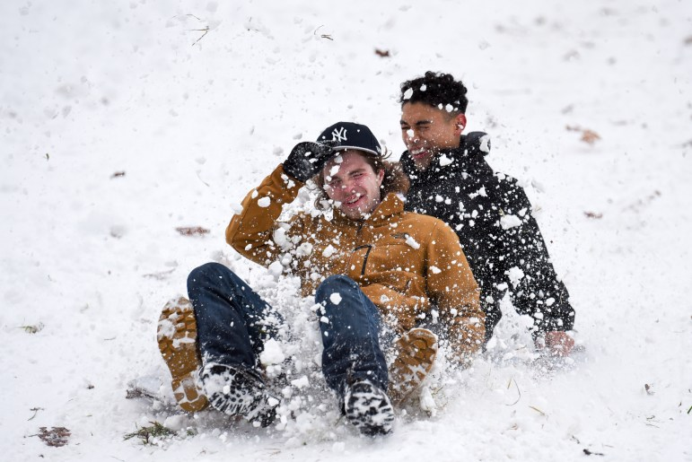 Jakob Richards '22, left, and Ryan Aguilar '22 slide down the slope on a flattened cardboard box. Although sledding down the slope has technically been banned since the 1970s, crowds of students gathered at the slope on Monday with makeshift sleds. (Boris Tsang/Sun Photography Editor)