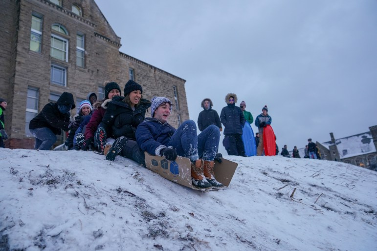 On Friday students flocked to Libe Slope to go sledding on the first snow day of the semester, using everything from toboggans to cardboard boxes. (Ben Parker/Sun Assistant Photography Editor)