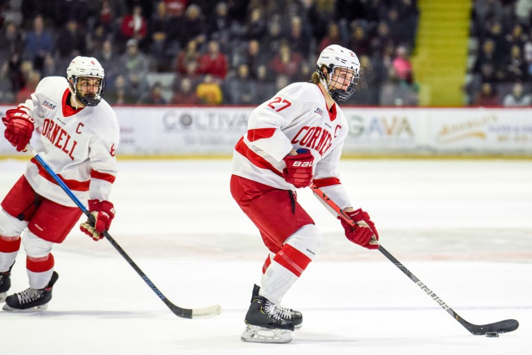 Men's hockey junior forward Morgan Barron, right, and junior defenseman Alex Green advance the puck at the game against RPI on Saturday. The game ended in a 4-2 Cornell win. (Boris Tsang/Sun Photography Editor)