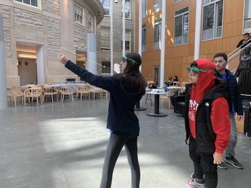 Two students test a plane for the elastic-launched gliders event in Klarman atrium.