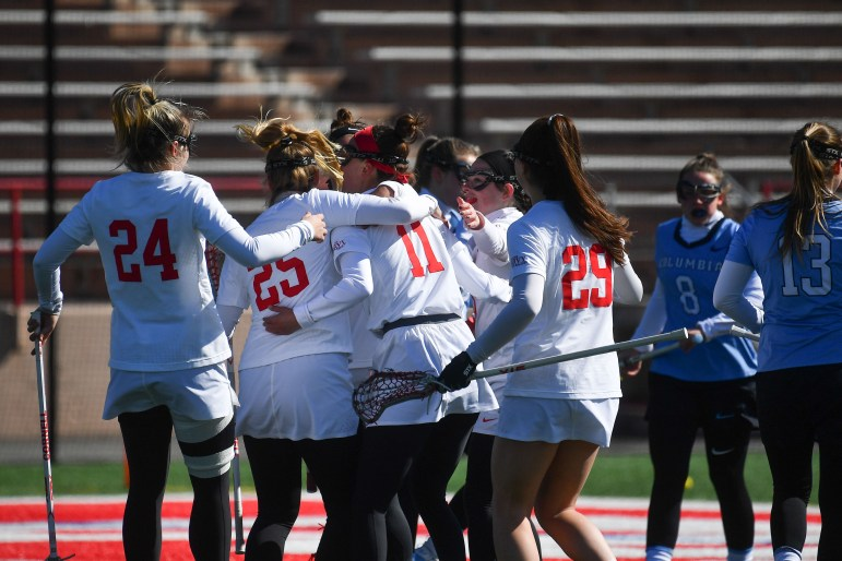 The women's lacrosse team celebrates their win against Columbia on Saturday. (Ben Parker/Sun Assistant Photography Editor)