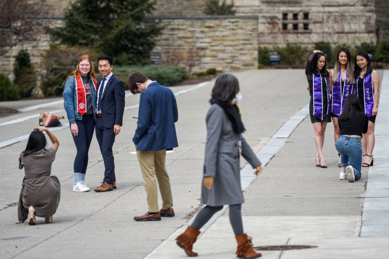Students take portraits on Ho Plaza as a woman wearing an N95 respirator walks past on March 18, 2020. Many seniors took advantage of the class suspension to take graduation photos on campus.
