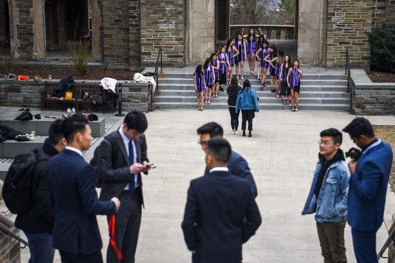 Members of alpha Kappa Delta Phi sorority posed for photos at Anabel Taylor Hall while another group waits for their picture opportunity on Wednesday.  Many seniors took advantage of the two-week class suspension to take graduation photos on campus. (Boris Tsang/Sun Photography Editor)