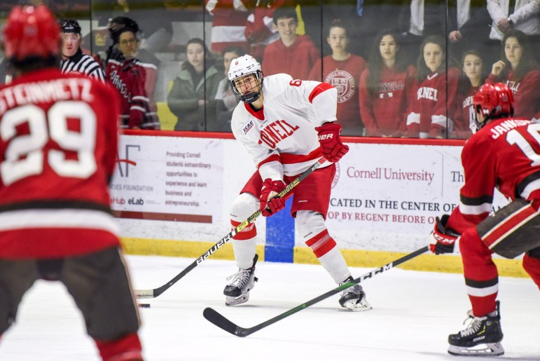 Junior defenseman Alex Green swipes the puck at the game against St. Lawrence on Friday. The game ended in a 5-0 Cornell win. (Boris Tsang/Sun Photography Editor)