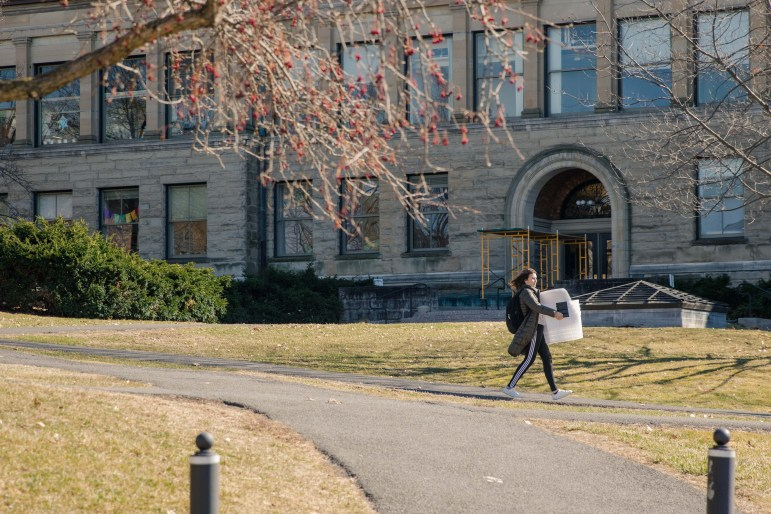 A student carries a stack of boxes across the Arts Quad Friday afternoon, after President Martha E. Pollack announced classes would end by 5 p.m.