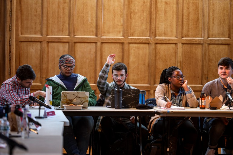 A Student Assembly member raises his hand at a meeting in Willard Straight Hall on Thursday. The Student Assembly unanimously voted against the university's proposal to rebrand HumEc as the School of Public Policy. (Michael Wenye Li/Sun Senior Photographer)