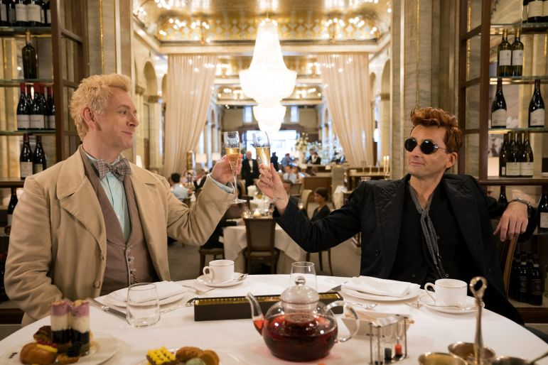 "An angel and a demon cheer to humanity in the Ritz hotel in ""Good Omens."""