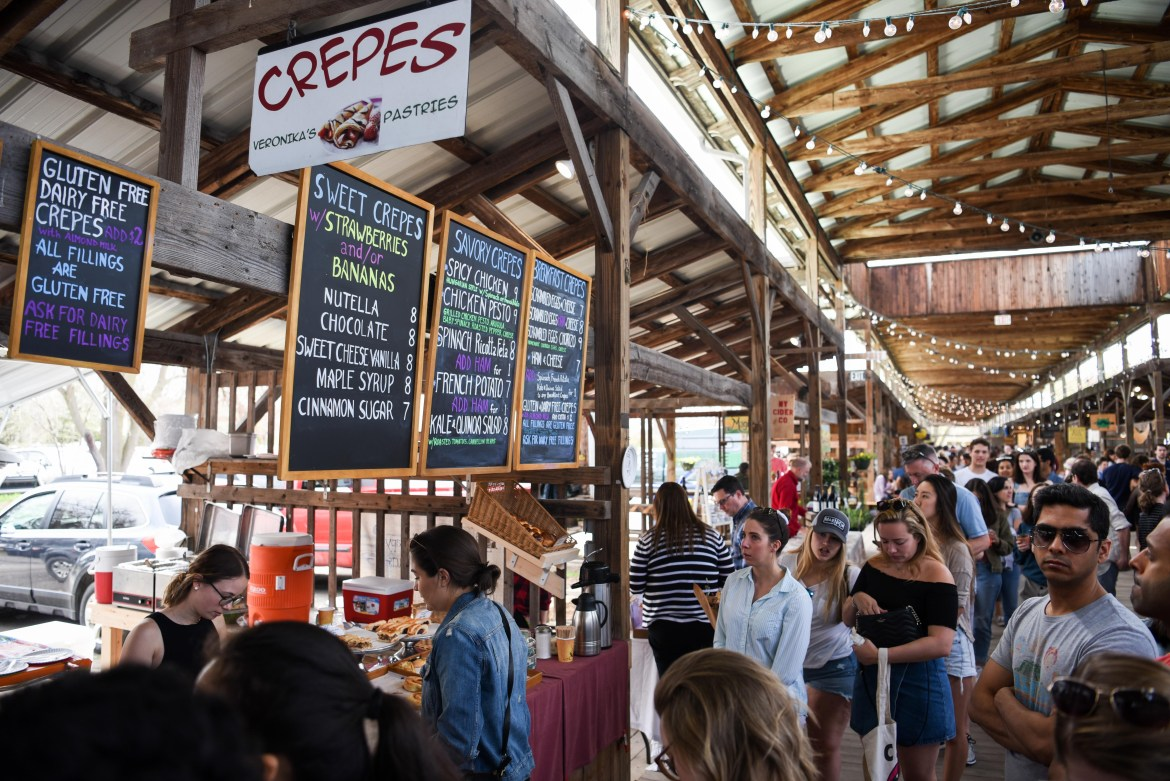 Customers pack into the Ithaca Farmers Market pavilion in April 2019. This season, the crowds are gone: Social distancing guidelines are in place, and the market reopened only as a grocery outlet.