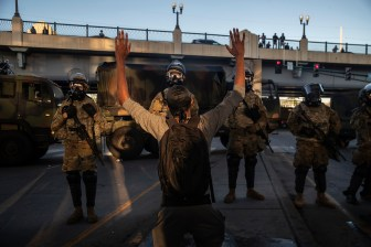 A demonstrator raises their hands as they stand off with members of the Minnesota National Guard, during a protest against the death of George Floyd and police brutality, in Minneapolis on May 29.