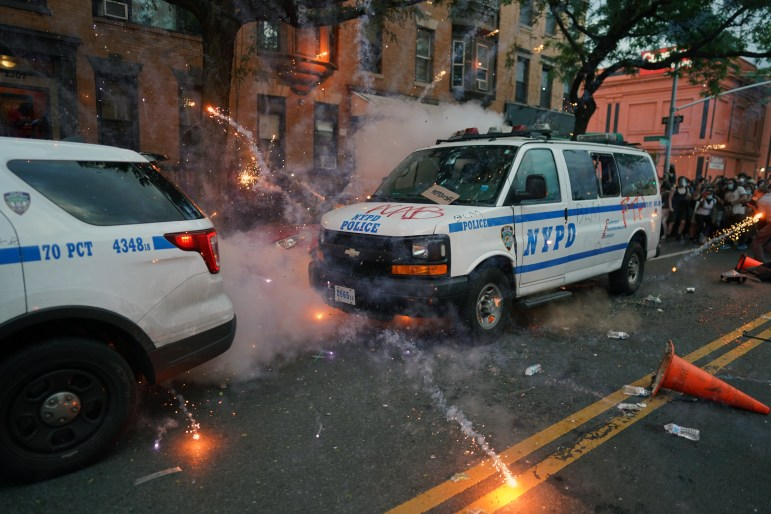 Fireworks explode around police vehicles during a protest rally in Brooklyn on May 30.