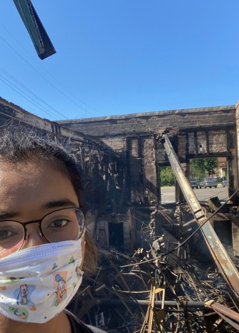 Chowdhury stands in front of a building that burned down during early Minneapolis protests.