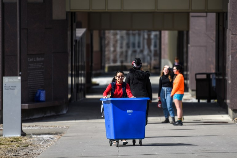 A student rolls a cart across West Campus on March 16, 2020.