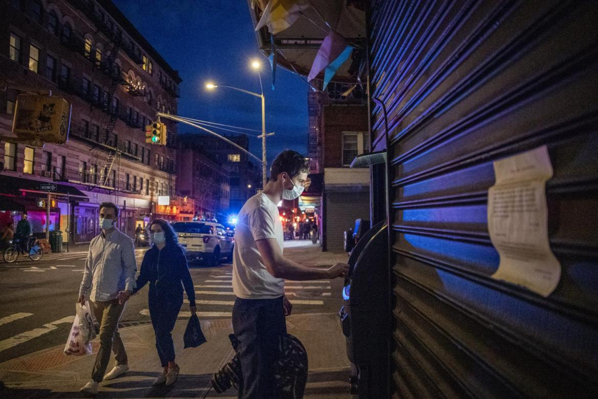 Man wears a mask while using an ATM in Manhattan's East Village neighborhood, April 7, 2020