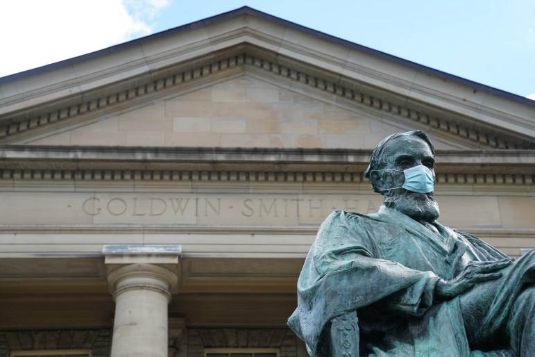 The A.D. White statue in front of Goldwin Smith Hall is outfitted with a mask. Life on campus is different, but Cornell's in-person plan has been one of the most successful in the country.