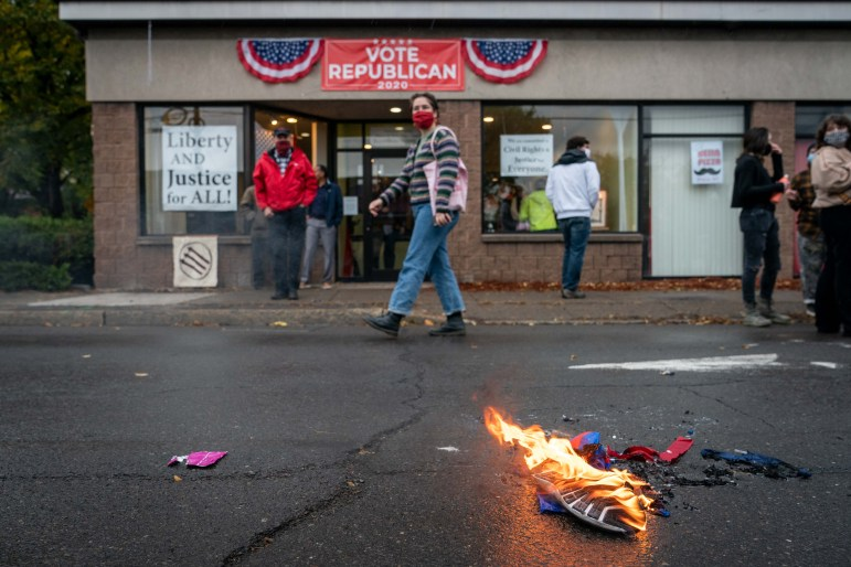 A shoe and a Trump 2020 flag burn in the middle of S Meadow Street, right outside the Tompkins County GOP headquarters.