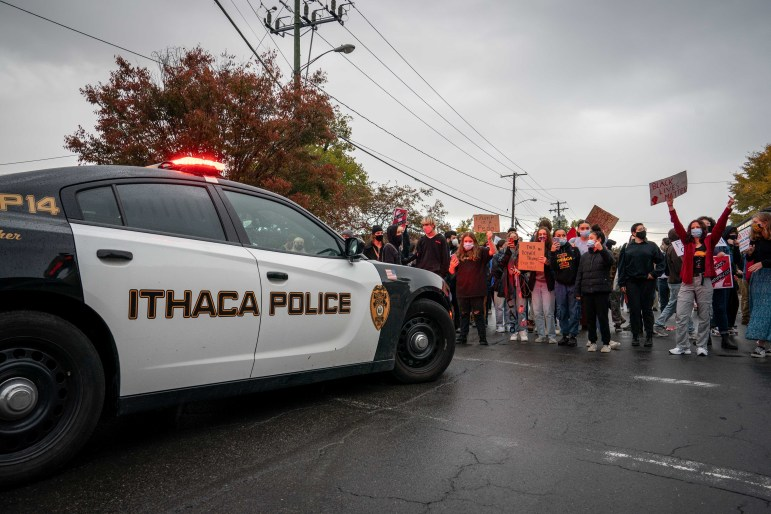 On Friday, counter-protestors at a Trump rally gather around parked Ithaca Police Department cars. There will be another Trump rally this Saturday.