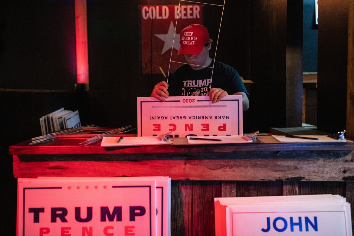 A volunteer with President Donald Trump's reelection campaign in Texas sets up yard signs at the Stampede Saloon in Fort Worth, Texas on Oct. 7, 2020.
