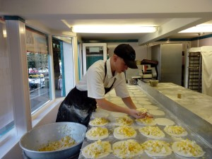 Man filling rows of pasties in Choak's Shop in Falmouth Cornwall