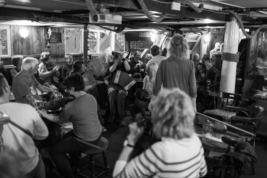 Black and white photograph by Lee J Palmer of musicians playing at the Admiral Benbow pub showing a packed out room with musicians clapping, dancers dancing and audience smiling.
