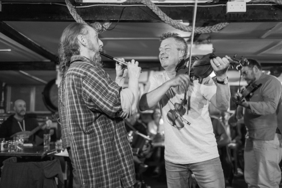 Black and white photograph by Lee J Palmer of two musicians playing at the Admiral Benbow pub, one a fiddle, the other a whistle.
