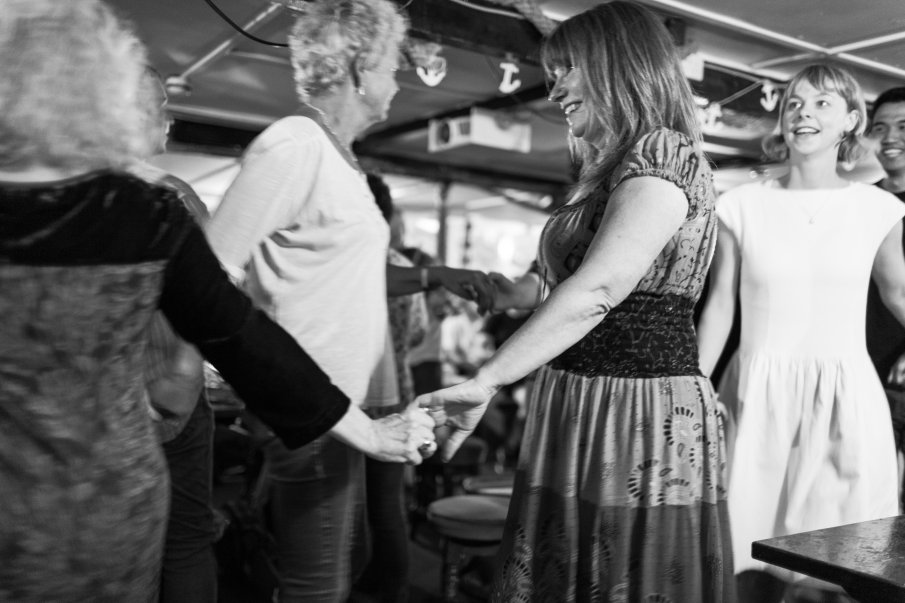 Black and white photograph by Lee J Palmer of dancers dancing hand in hand to Cornish music by musicians playing at the Admiral Benbow pub.