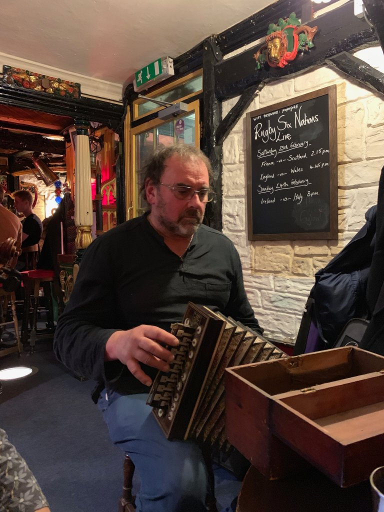 Man playing a flutina in the Admiral Benbow pub.