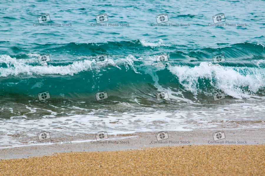 Wave breaking on the shoreline on Marazion Beach in Cornwall