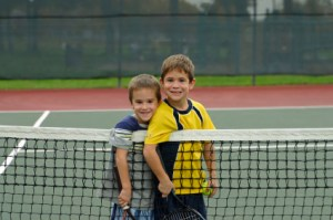 Two small boys at a tennis net