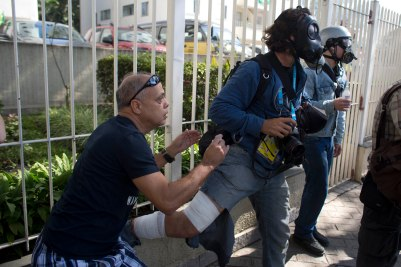 Peru-based AP photographer Rodrigo Abd, places his gas mask back on as violence resumes while being treated by a friendly bystander doctor, left, after he suffered injuries during an Anti-World Cup protest on the opening day of the World Cup in Sao Paulo, Brazil, Thursday, June 12, 2014. (AP Photo/Dario Lopez-Mills)