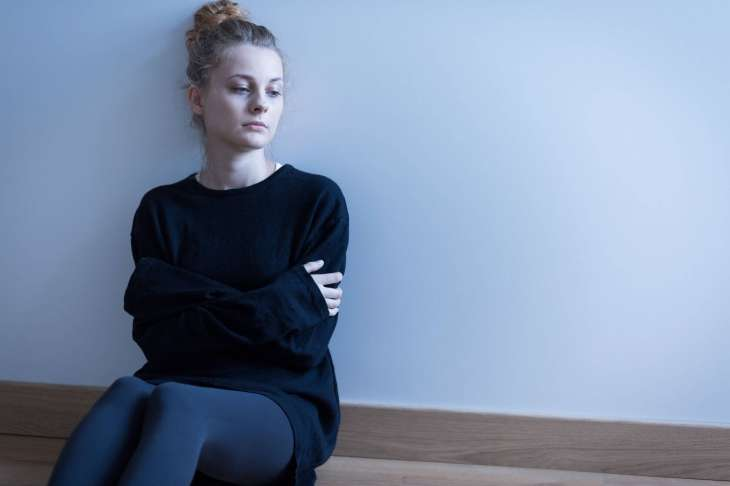 a young woman sits on the floor, crippled by social anxiety