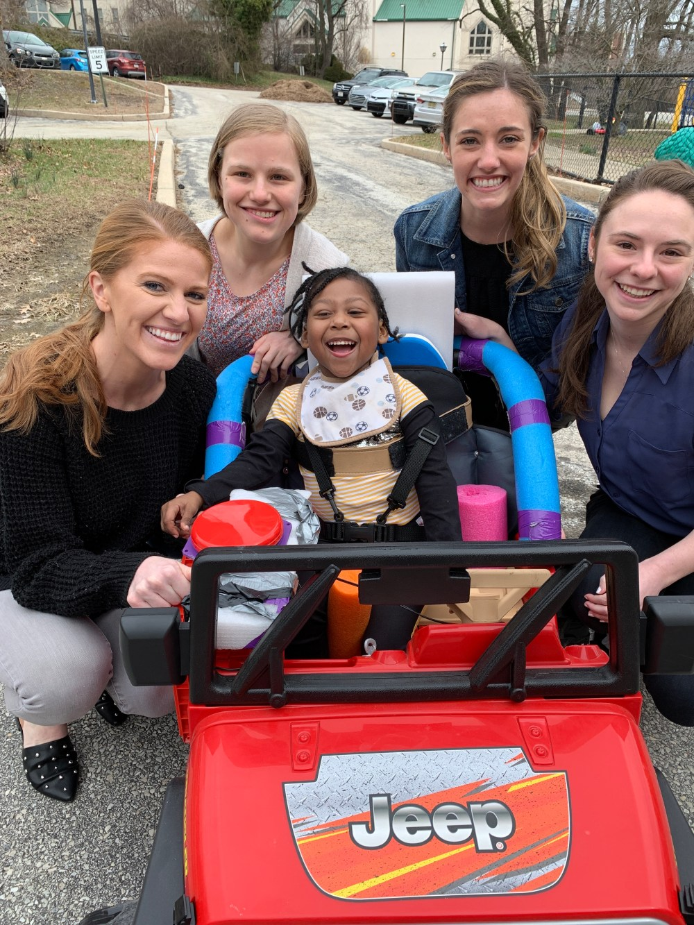 Ariel poses in her new Jeep with students from Jefferson University.